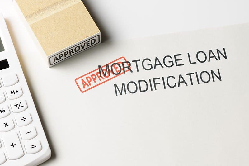"""Close-up of mortgage modification with """"Approved """" rubber stamp with calculator."""