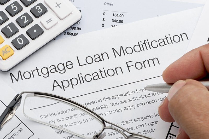 Close up Mortgage loan modification application form with calculator, pen and glasses